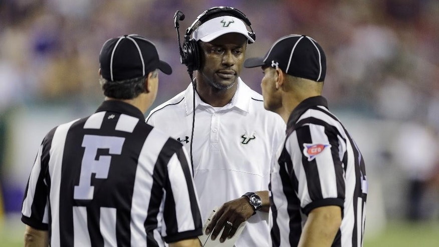 South Florida head coach Willie Taggart, center, talks to field judge Rick Santilli, left, and line judge Baron Ballester during the fourth quarter of an NCAA college football game against East Carolina, Saturday, Oct. 11, 2014, in Tampa, Fla. (AP Photo/Chris O'Meara)