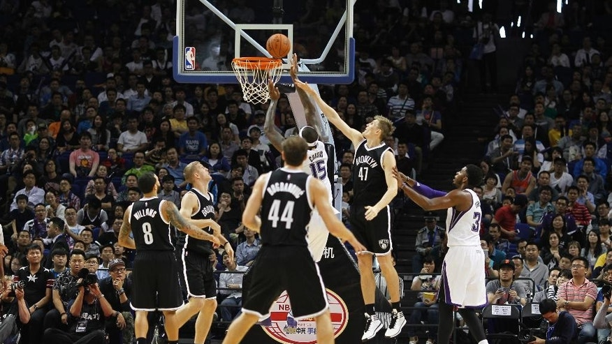 Brooklyn Nets' Sergey Karasev,  black, competes with Sacramento Kings' DeMarcus Cousins in white (15) during a NBA exhibition game in Shanghai, China Sunday, Oct. 12, 2014. Nets defeated Kings 97-95. (AP Photo)