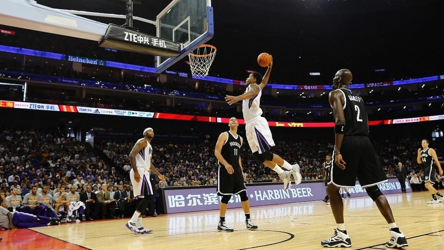 Sacramento Kings' Rudy Gay jumps to slam-dunk against the Brooklyn Nets during a NBA global game in Shanghai, China Sunday, Oct. 12, 2014.  Nets defeated Kings 97-95. (AP Photo)