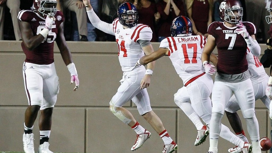 Mississippi quarterback Bo Wallace (14) celebrates with Evan Engram (17) after scoring during the first quarter of an NCAA college football game Saturday, Oct. 11, 2014, in College Station, Texas. (AP Photo/Bob Levey)