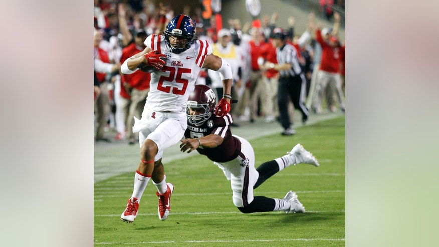 Mississippi defensive back Cody Prewitt (25) avoids a tackle attempt by Texas A&M quarterback Kenny Hill (7) as he returns an interception for a 75-yard touchdown during the second quarter of an NCAA college football game Saturday, Oct. 11, 2014, in College Station, Texas. (AP Photo/Bob Levey)