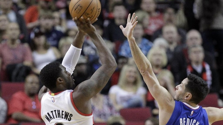 Portland Trail Blazers guard Wesley Matthews, left, shoots over Los Angeles Clippers guard J.J. Redick during the first half of an NBA pre-season basketball game in Portland, Ore., Sunday, Oct. 12, 2014.(AP Photo/Don Ryan)