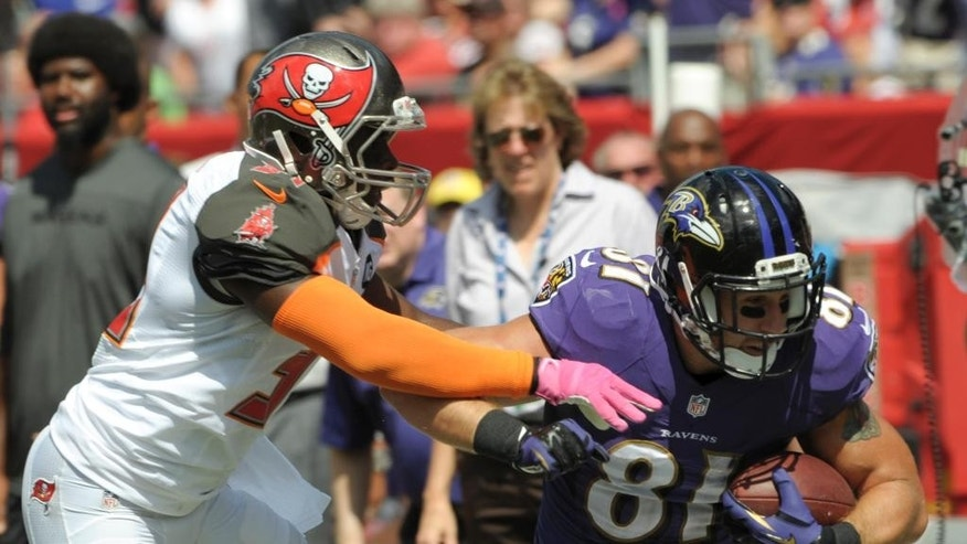 Baltimore Ravens tight end Owen Daniels (81) runs for yardage after a reception as Tampa Bay Buccaneers cornerback Major Wright tries to make the tackle during the first half of an NFL football game in Tampa, Fla., Sunday, Oct. 12, 2014. (AP Photo/Steve Nesius)