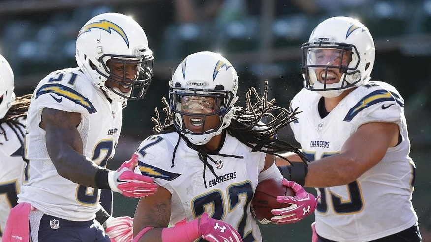 San Diego Chargers cornerback Jason Verrett (22) celebrates with cornerback Richard Marshall, left, and inside linebacker Andrew Gachkar (59) after intercepting Oakland Raiders quarterback Derek Carr during the fourth quarter of an NFL football game in Oakland, Calif., Sunday, Oct. 12, 2014. The Chargers won 31-28. (AP Photo/Ben Margot)