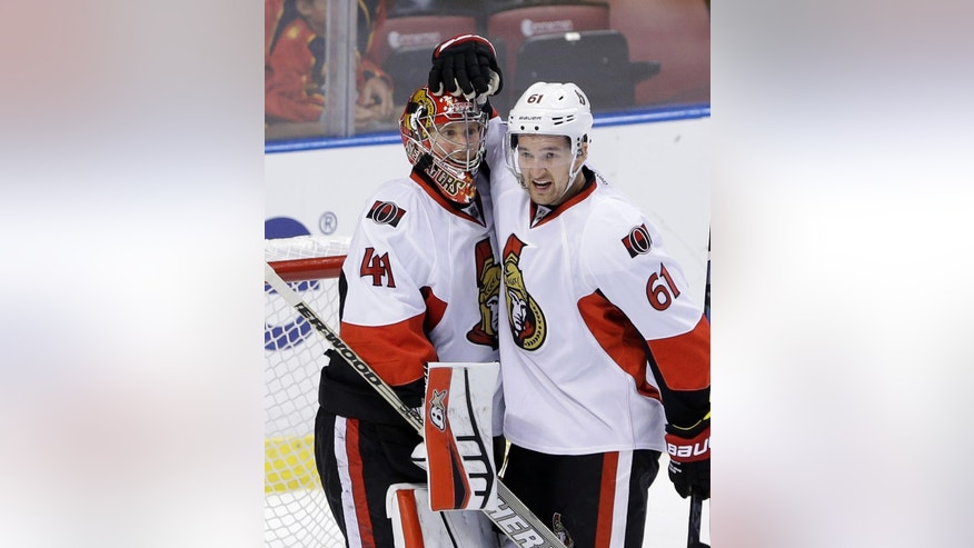 Ottawa Senators goalie Craig Anderson (41) and right wing Mark Stone (61) celebrate after the Senators defeated the Florida Panthers 1-0 in an NHL hockey game, Monday, Oct. 13, 2014 in Sunrise, Fla. (AP Photo/Wilfredo Lee)
