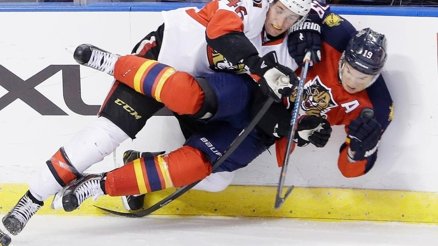 Ottawa Senators defenseman Patrick Wiercioch (46) slams Florida Panthers right wing Scottie Upshall (19) into the boards during the first period of an NHL hockey game, Monday, Oct. 13, 2014 in Sunrise, Fla. (AP Photo/Wilfredo Lee)