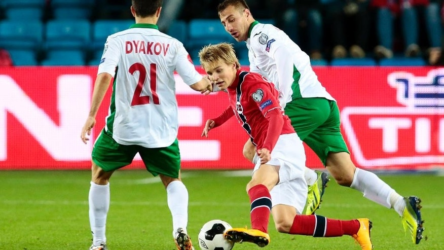 Norway's youngest player, Martin Odegaard, centre, avoids Bulgaria's Svetoslav Dyakov, left, during the Euro 2016 Group H qualifying soccer match between Norway and Bulgaria at Ullevaal Stadium in Oslo Monday, Oct. 13, 2014. (AP Photo/NTB Scanpix, Hakon Mosvold Larsen)  NORWAY OUT