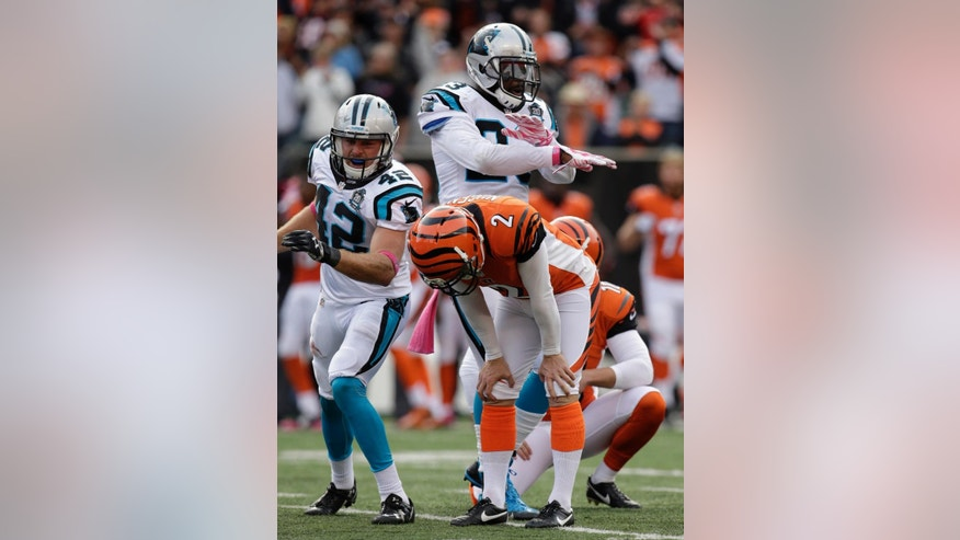 Carolina Panthers quarterback Cam Newton (1) runs through Cincinnati Bengals cornerback Terence Newman (23) and outside linebacker Vontaze Burfict (55) for a 12-yard touchdown in the second half of an NFL football game, Sunday, Oct. 12, 2014, in Cincinnati. (AP Photo/Paul Sancya)