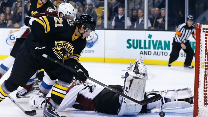 Boston Bruins left wing Loui Eriksson (21), of Sweden, sends the puck into the net as Colorado Avalanche goalie Reto Berra lays on the ice after being drawn out of position in the second period of an NHL hockey game in Boston, Monday, Oct. 13, 2014. (AP Photo/Elise Amendola)
