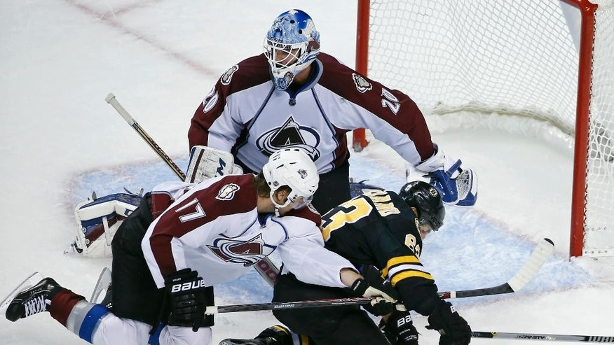 Colorado Avalanche's Brad Stuart (17) keeps Boston Bruins left wing Brad Marchand (63) from scoring against Avalanche goalie Reto Berra (20) in the first period of an NHL hockey game in Boston, Monday, Oct. 13, 2014. (AP Photo/Elise Amendola)