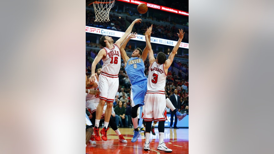 Chicago Bulls forward Pau Gasol (16) blocks the shot of Denver Nuggets forward Danilo Gallinari (8) as Chicago Bulls forward Doug McDermott (3) defends during the first half of a pre-season NBA basketball game in Chicago, on Monday Oct. 13, 2014. (AP Photo/Jeff Haynes)