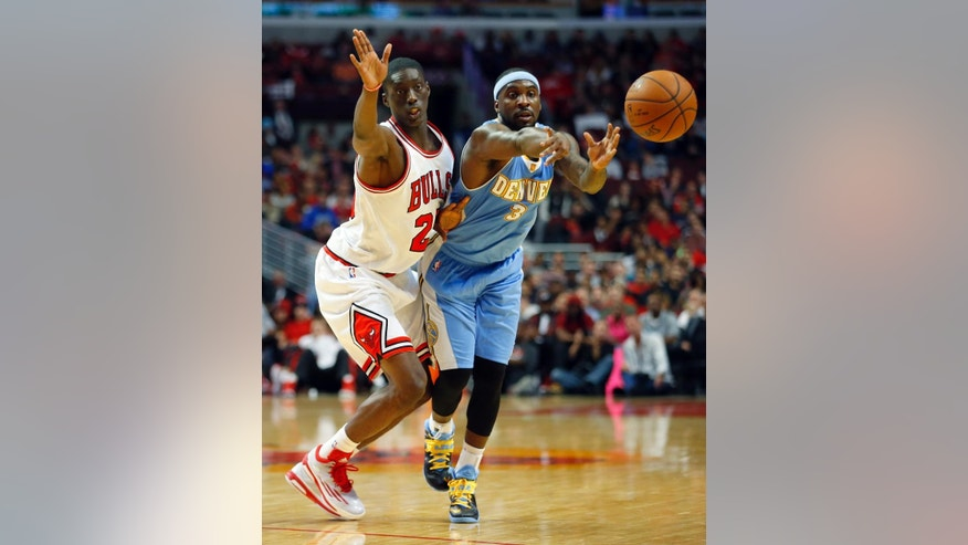 Chicago Bulls forward Tony Snell (20) guards Denver Nuggets guard Ty Lawson (3) as Lawson makes a pass during the first half of a pre-season NBA basketball game in Chicago, on Monday Oct. 13, 2014. (AP Photo/Jeff Haynes)