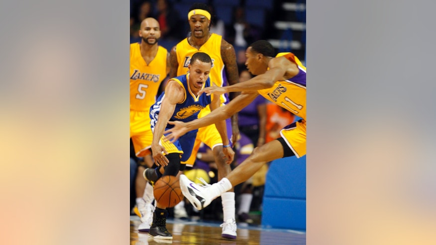 Golden State Warriors guard Stephen Curry (30) battles for the ball against Los Angeles Lakers forwards Wesley Johnson, right, with Carlos Boozer (5) and Jordan Hill looking on during the first half of a preseason NBA basketball game, Sunday, Oct. 12, 2014, in Ontario, Calif. (AP Photo/Alex Gallardo)
