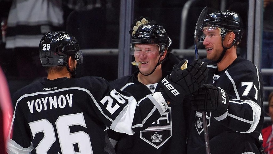 Los Angeles Kings center Jeff Carter, right, celebrates his goal with center Tyler Toffoli, center, and defenseman Slava Voynov, of Russia, during the second period of a NHL hockey game against the Winnipeg Jets, Sunday, Oct. 12, 2014, in Los Angeles, Calif. (AP Photo/Mark J. Terrill)