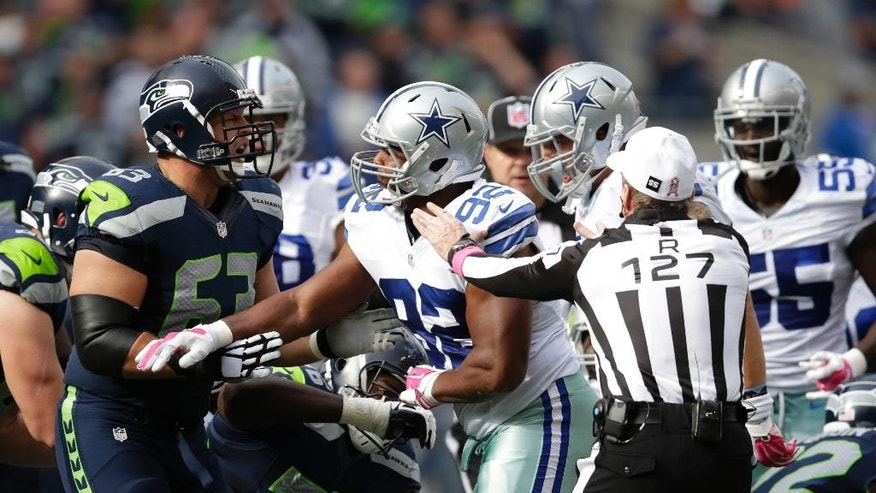 Seattle Seahawks guard Stephen Schilling, left, and Dallas Cowboys defensive end Jeremy Mincey (92) exchange words and shoves as referee Bill Leavy (127) moves in to stop it in the second half of an NFL football game, Sunday, Oct. 12, 2014, in Seattle. (AP Photo/Scott Eklund)