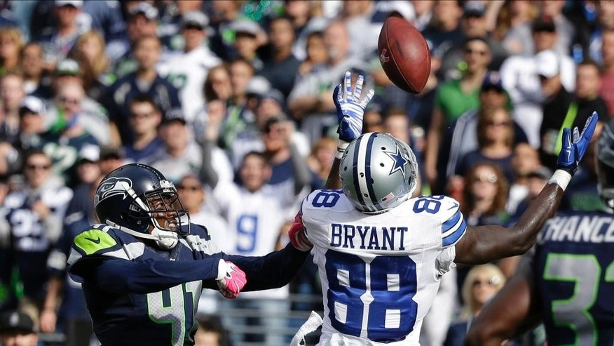 Seattle Seahawks cornerback Byron Maxwell, left, breaks up a pass reception to Dallas Cowboys wide receiver Dez Bryant (88) in the first half of an NFL football game, Sunday, Oct. 12, 2014, in Seattle. (AP Photo/Elaine Thompson)