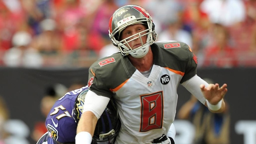 Tampa Bay Buccaneers quarterback Mike Glennon (8) is hit by Baltimore Ravens inside linebacker C.J. Mosley (57) after throwing a pass during the first half of an NFL football game in Tampa, Fla., Sunday, Oct. 12, 2014. (AP Photo/Steve Nesius)