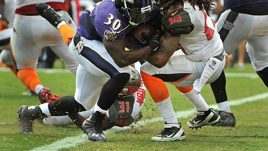 Baltimore Ravens running back Bernard Pierce (30) pushes his way past Tampa Bay Buccaneers strong safety Mark Barron (23) for a touchdown on a 4-yard run during the second half of an NFL football game in Tampa, Fla., Sunday, Oct. 12, 2014. (AP Photo/Steve Nesius)