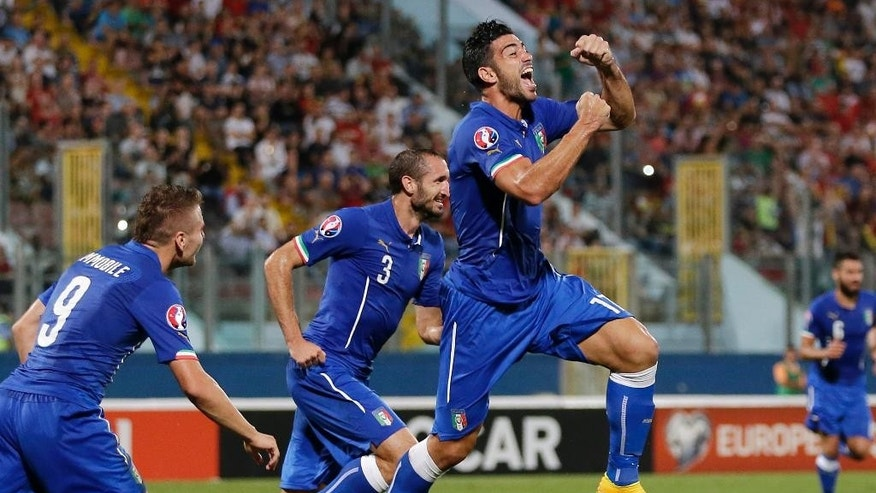 Italy's Graziano Pelle, right, celebrates with his teammates Ciro Immobile, left, and Giorgio Chiellini after scoring during the Euro 2016 qualifying soccer match between Malta and Italy, at the National Stadium Ta' Qali, in Valletta, Malta, Monday, Oct. 13, 2014. (AP Photo/Antonio Calanni)