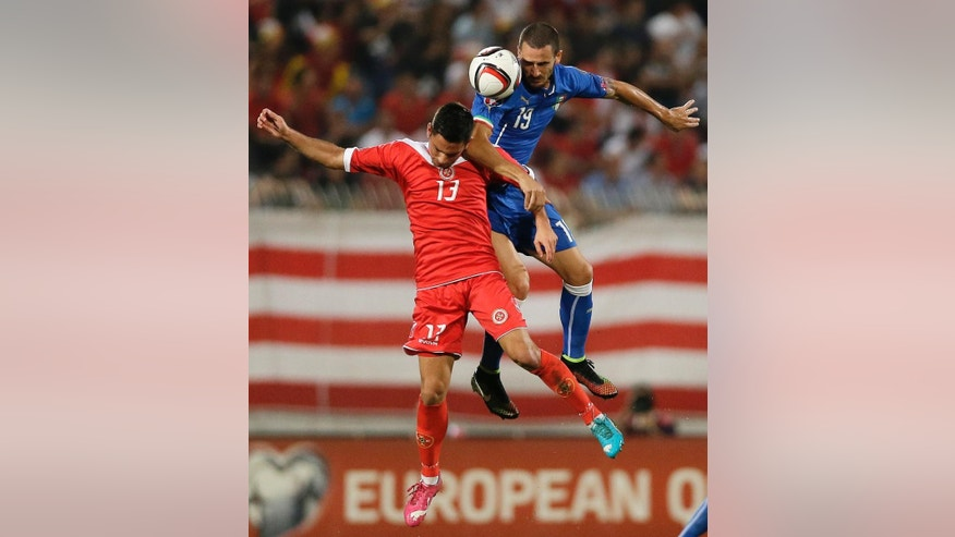 Italy's Leonardo Bonucci, top, jumps for the ball with Malta's Andre Schembri during the Euro 2016 qualifying soccer match between Malta and Italy, at the National Stadium Ta' Qali, in Valletta, Malta, Monday, Oct. 13, 2014. (AP Photo/Antonio Calanni)