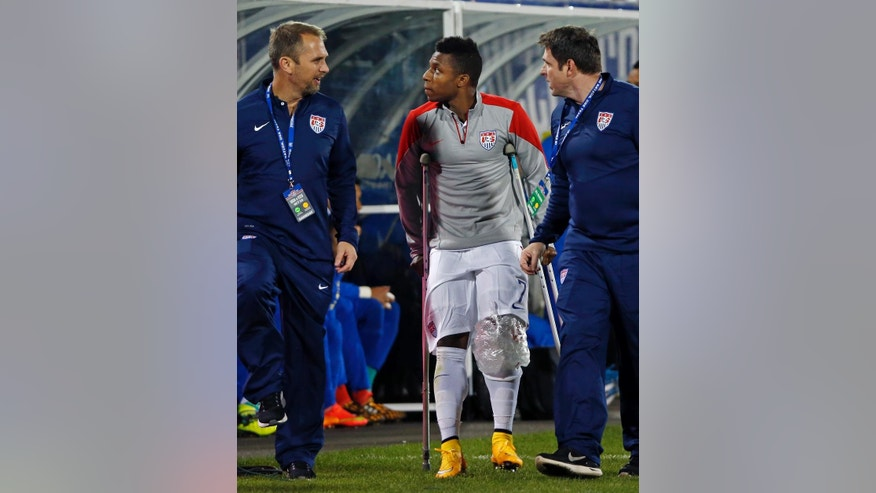 United States' Joe Gyau (7) is accompanied by trainers as he walks off the field on crutches after injuring his knee during the firs thalf of an exhibition soccer match against Ecuador in East Hartford, Conn., Friday, Oct. 10, 2014. Gyau sprained his left knee, according to US Soccer. (AP Photo/Elise Amendola)
