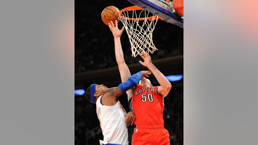Toronto Raptors center Tyler Hansbrough (50) is fouled by New York Knicks forward Carmelo Anthony during the first quarter of an NBA basketball game Monday, Oct. 13, 2014, at Madison Square Garden in New York. (AP Photo/Bill Kostroun)