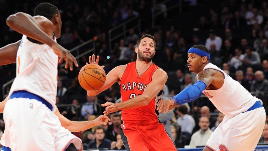 Toronto Raptors guard Greivis Vasquez, center, passes the ball as he is guarded by New York Knicks forward Carmelo Anthony, right, during the first quarter of an NBA basketball game Monday, Oct. 13, 2014, at Madison Square Garden in New York. (AP Photo/Bill Kostroun)