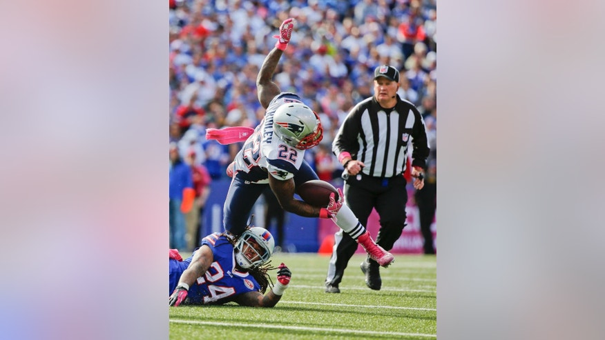 New England Patriots running back Stevan Ridley (22) falls over Buffalo Bills' Stephon Gilmore (24) during the second half of an NFL football game Sunday, Oct. 12, 2014, in Orchard Park, N.Y. Ridley was injured on the play. (AP Photo/Mike Groll)
