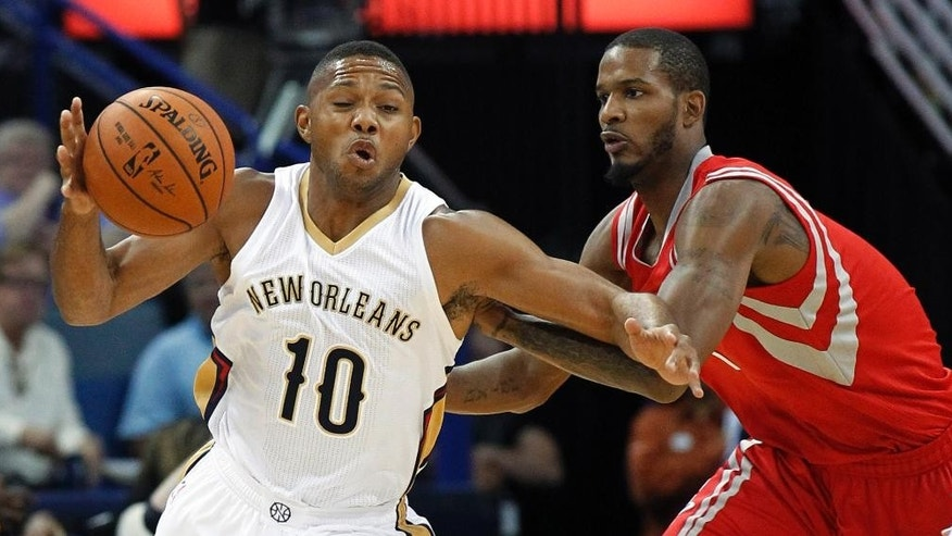 New Orleans Pelicans guard Eric Gordon (10) reacts after being fouled by Houston Rockets guard Trevor Ariza during the first half of an NBA preseason basketball game in New Orleans, Tuesday, Oct. 14, 2014. (AP Photo/Bill Haber)