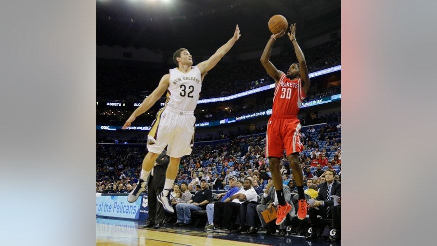 Houston Rockets guard Troy Daniels (30) shoots over New Orleans Pelicans guard Jimmer Fredette (32) during the first half of an NBA preseason basketball game in New Orleans, Tuesday, Oct. 14, 2014. (AP Photo/Bill Haber)