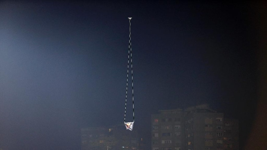 A drone flies over the Partizan stadium during the Euro 2016 Group I qualifying match between Serbia and Albania in Belgrade, Serbia, Tuesday, Oct. 14, 2014. A European Championship qualifier between Serbia and Albania was suspended on Tuesday after pitch skirmishes involving players and fans over an Albanian flag that was flown above the stadium by a drone. (AP Photo/Marko Drobnjakovic)