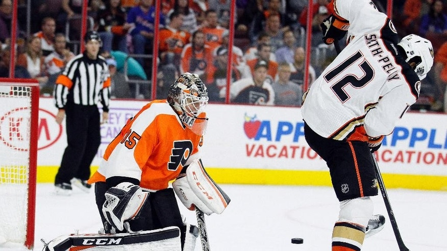 The Anaheim Ducks' Devante Smith-Perry (12), right, directs the puck past Philadelphia Flyers' goalie Steve Mason (35) and into the net for a goal during the first period of an NHL hockey game  Tuesday, Oct. 14, 2014, in Philadelphia. (AP Photo/Tom Mihalek)