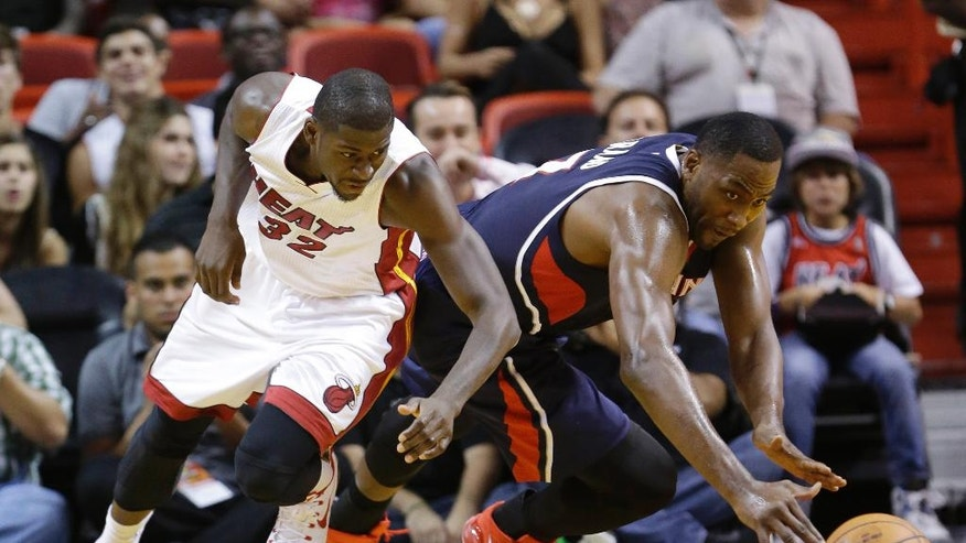 Miami Heat forward James Ennis (32) and Atlanta Hawks forward Elton Brand battle for a loose ball during the first half of a preseason NBA basketball game, Tuesday, Oct. 14, 2014 in Miami. (AP Photo/Wilfredo Lee)