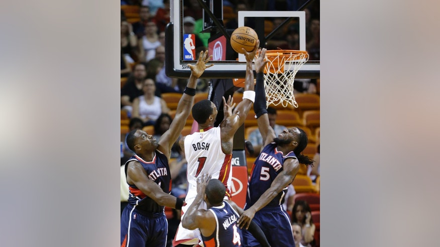 Atlanta Hawks forward Elton Brand, left, and forward DeMarre Carroll (5) and forward Paul Millsap (4) attempt to block a shot by Miami Heat forward Chris Bosh (1) during the first half of a preseason NBA basketball game, Tuesday, Oct. 14, 2014 in Miami. (AP Photo/Wilfredo Lee)