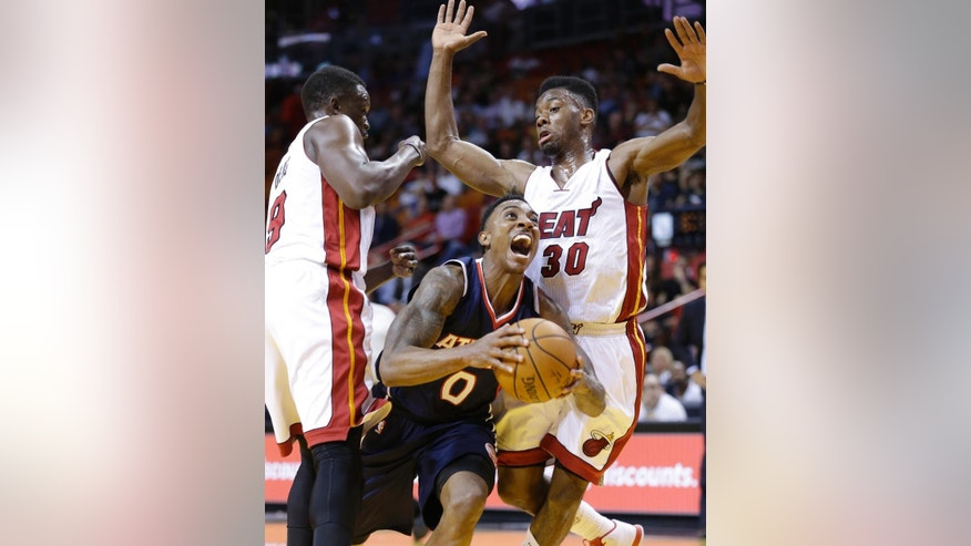 Atlanta Hawks guard Jeff Teague (0) goes up for a shot against Miami Heat forward Luol Deng (9) of Sudan, and guard Norris Cole (30) during the first half of a preseason NBA basketball game, Tuesday, Oct. 14, 2014 in Miami. (AP Photo/Wilfredo Lee)