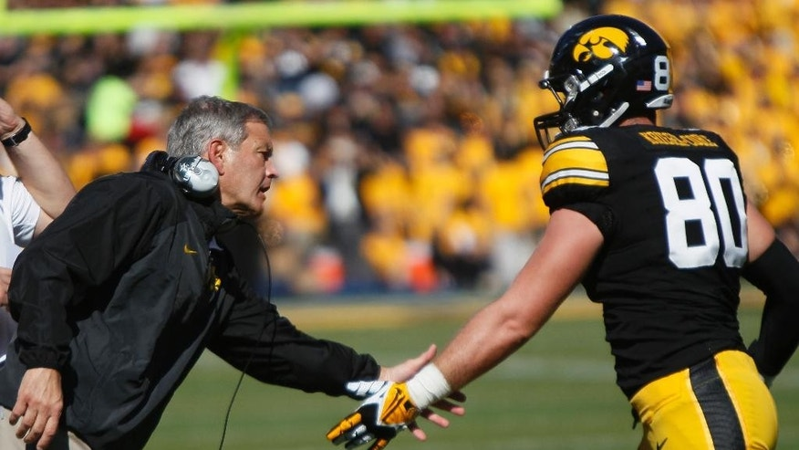 Iowa head coach Kirk Ferentz congratulates tight end Henry Krieger Coble after a successful extra point during the second half of an NCAA college football game against Indiana, Saturday, Oct. 11, 2014, in Iowa City, Iowa. Iowa won 45-29. (AP Photo/Matthew Putney)