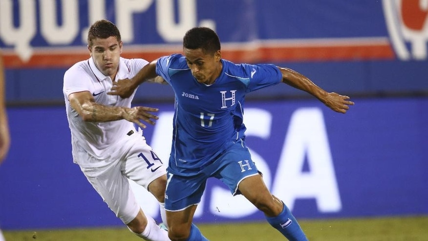 U.S. Nation Team's Greg Garza (14) and Honduras' Andy Najar (17) battle for the ball during the first half of  an international friendly  in Boca Raton, Fla., Tuesday, Oct. 14, 2014. (AP Photo/J Pat Carter)