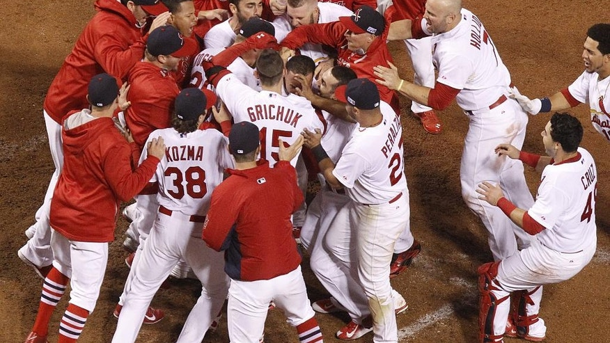In this Sunday, Oct. 12, 2014, photo, St. Louis Cardinals mob teammate Kolten Wong after his game-winning leadoff home run in the ninth inning during Game 2 of the National League Championship Series against the San Francisco Giants at Busch Stadium in St. Louis. The Cardinals beat the Giants 5-4 to even the best-of-seven series at a game apiece. (AP Photo/St. Louis Post-Dispatch, Cliff Lee)  EDWARDSVILLE INTELLIGENCER OUT; THE ALTON TELEGRAPH OUT