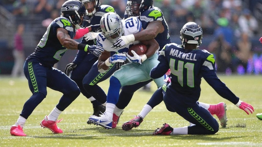 Dallas Cowboys running back Joseph Randle (21) is tackled by Seattle Seahawks defensive tackle Tony McDaniel, upper right, in the first half of an NFL football game, Sunday, Oct. 12, 2014, in Seattle. (AP Photo/Scott Eklund)
