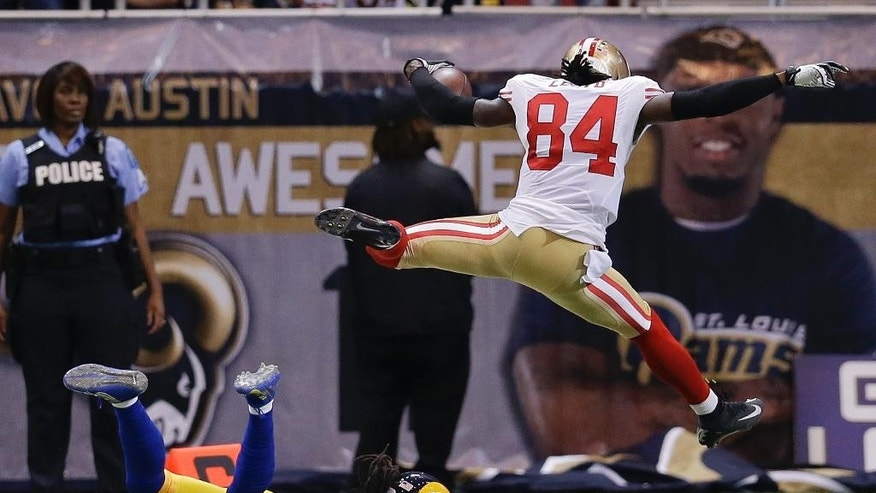 San Francisco 49ers wide receiver Brandon Lloyd (84) jumps into the end zone ahead of St. Louis Rams cornerback Janoris Jenkins (21) as Lloyd scores a touchdown on an 80-yard pass play in the second quarter of an NFL football game Monday, Oct. 13, 2014, in St Louis. (AP Photo/Scott Kane)