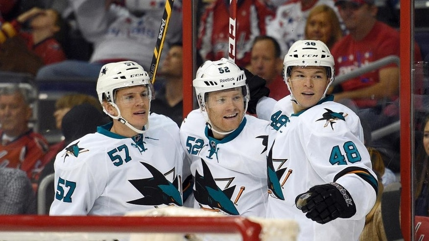 San Jose Sharks defenseman Matt Irwin (52) celebrates his goal with Tommy Wingels (57) and Tomas Hertl (48), of the Czech Republic, against the Washington Capitals during the first period of an NHL hockey game, Tuesday, Oct. 14, 2014, in Washington. (AP Photo/Nick Wass)