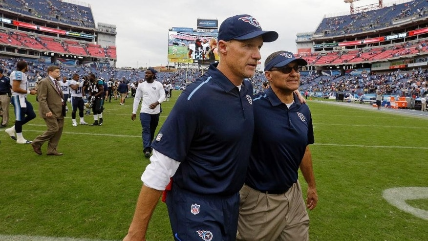 Tennessee Titans head coach Ken Whisenhunt, center, leaves the field after the Titans beat the Jacksonville Jaguars 16-14 in an NFL football game Sunday, Oct. 12, 2014, in Nashville, Tenn. (AP Photo/Wade Payne)