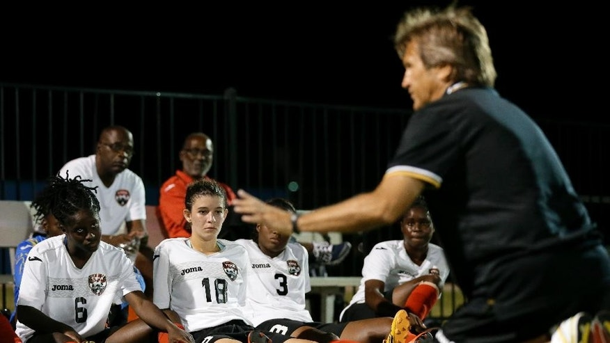 Trinidad & Tobago women's national soccer team head coach Randy Waldrum, right, instructs Khadidra DeBessette (6), Anique Walker (18), Mariah Shade (3) and the rest of the team at half time of an exhibition soccer scrimmage against FC Dallas' U-18 women's team at Toyota Stadium Complex,  Thursday, Oct. 9, 2014, in Frisco, Texas. (AP Photo/Tony Gutierrez)
