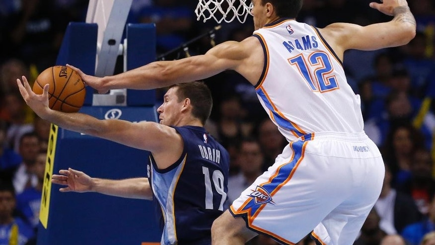 Oklahoma City Thunder center Steven Adams (12) blocks a shot from behind by Memphis Grizzlies guard Beno Udrih (19) in the second quarter of an NBA basketball pre-season game in Oklahoma City, Tuesday, Oct. 14, 2014. (AP Photo/Sue Ogrocki)