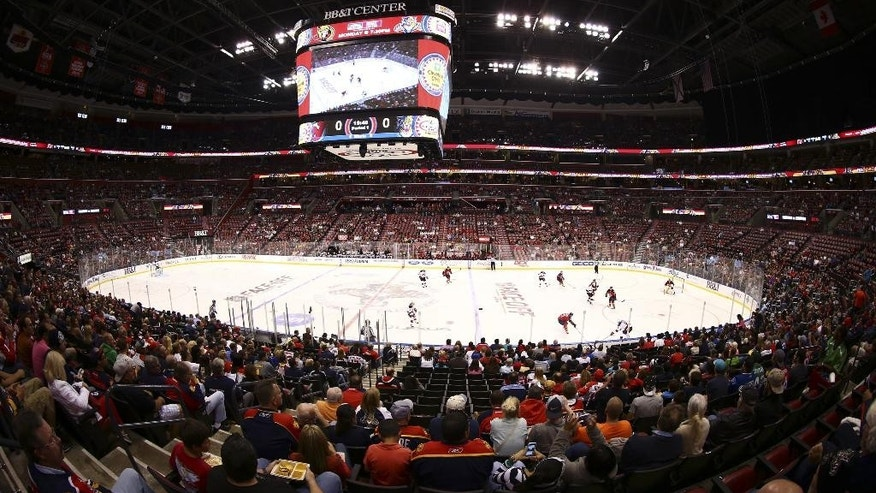 RETRANSMITTING FOR IMPROVED QUALITY In this image made with a fisheye lens, Florida Panthers hockey fans watch game  action against the New Jersey Devils during the first period of a NHL hockey game in Sunrise, Fla., Saturday, Oct. 11, 2014. (AP Photo/J Pat Carter)