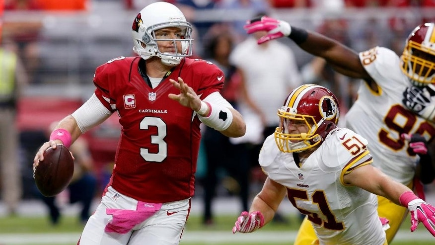Arizona Cardinals quarterback Carson Palmer (3) eludes the pressure of Washington Redskins inside linebacker Will Compton (51) during the first half of an NFL football game, Sunday, Oct. 12, 2014, in Glendale, Ariz.(AP Photo/Ross D. Franklin)