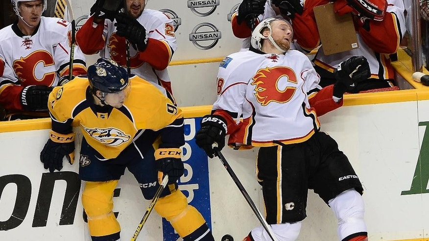 Nashville Predators center Filip Forsberg (9) checks into the board Calgary Flames center Matt Stajan (18) as they try to get control of the puck in the second period of an NHL hockey game Tuesday, Oct. 14, 2014, in Nashville, Tenn. (AP Photo/Mark Zaleski)