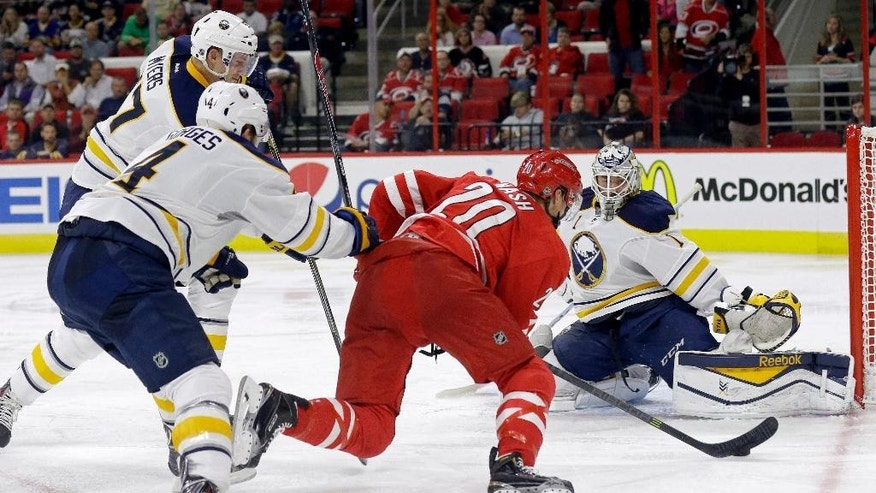 Carolina Hurricanes' Riley Nash (20) tries to score against Buffalo Sabres goalie Jhonas Enroth (1), of Sweden, as Sabres' Tyler Myers, left, and Josh Gorges (4) defend during the second period of an NHL hockey game in Raleigh, N.C., Tuesday, Oct. 14, 2014. (AP Photo/Gerry Broome)
