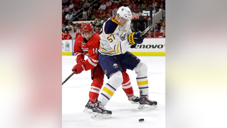Carolina Hurricanes' Nathan Gerbe (14) and Buffalo Sabres' Tyler Myers (57) skate for the puck during the second period of an NHL hockey game in Raleigh, N.C., Tuesday, Oct. 14, 2014. (AP Photo/Gerry Broome)