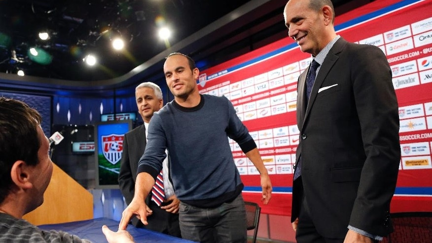 In this Oct. 10, 2014, photo, Major League Soccer Commissioner Don Garber, right, watches Landon Donovan shake a hand as he and Sunil Gulati, left, president of the U.S. Soccer Federation, wrap up a news conference in Bristol, Conn. Garber took the extraordinary step Wednesday, Oct. 15, 2014, of criticizing U.S. coach Jurgen Klinsmann for not taking Landon Donovan to the World Cup and for saying Clint Dempsey and Michael Bradley damaged their careers by returning to MLS from European clubs. Garber, the league's commissioner since 1999, questioned whether Klinsmann could be an effective coach while publicly criticizing MLS. (AP Photo/Elise Amendola)